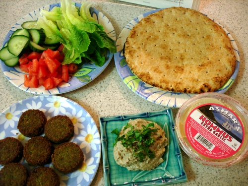 the spread - cucumber, romaine, tomatoes, pita, hummus, baba ghanouj, and falafel